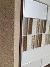 glass tile backsplash with a satin nickel schluter metal edge trim