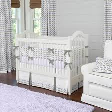 white wooden crib with white gray zigzag bedding placed on the dark brown wooden flooring plus