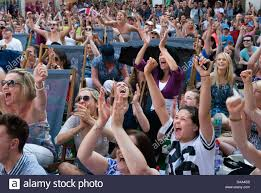 sports fans cheering. stock photo - watching sport cheering crowd of sports fans wimbledon town center on tv screen uk homer sykes