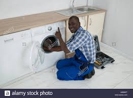 black man washing clothes.  Black Closeup Of Young Happy African Technician Fixing Washing Machine  Stock  Image On Black Man Clothes