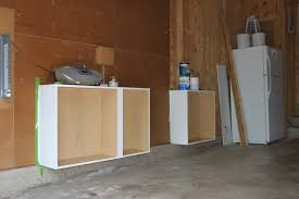 unfinished garage makeover design with wood wall panels cover plus simple custom diy mounted garage cabinet without door beside refrigerator ideas
