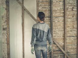 a young woman is standing in a loft room and is looking at the insulation she
