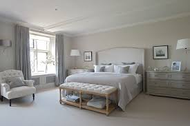 spacious bedroom with wide nightstands and grey bed near tufted end of bed bench bed bench furniture