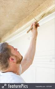 professional painter cutting in with brush to paint garage door frame royalty free stock image