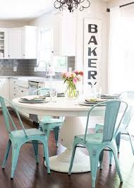 a chic breakfast nook with a large white pedestal table and blue metal chairs looks very
