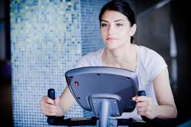 woman riding an exercise bike in gym cardio and fat loss