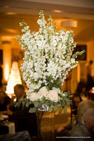 tall centerpiece in clear glass vase with bunches of white stock cream roses and green