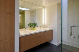 view in gallery light cherry wood vanity with white countertop and sidelights on the mirror