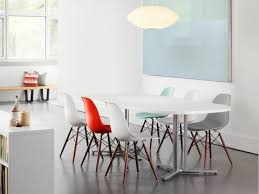 an open meeting area featuring an oval everywhere table and eames molded plastic chairs in various