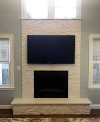 white stone fireplace | Finished nor-stone fireplace with mounted TV in  Lexington MA.