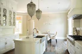 stunning kitchen features a pair of french pendants hanging over an island topped with white marble fitted with a stainless steel a sink and satin
