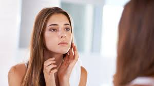woman staring at complexion in mirror yuri arcurs wondering how to get rid of acne fast