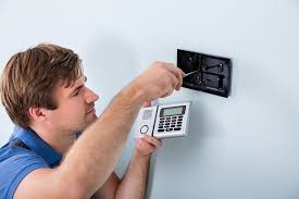 man installing a diy home security system