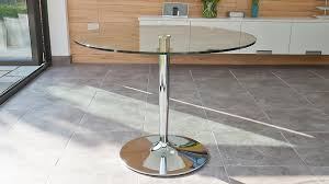 round glass four seater dining table with a chrome pedestal base