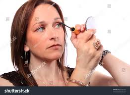 woman holding hand mirror. Woman Holding Hand Mirror Applies Mascara To Eyelashes L