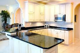 these beautiful granite counters break up the brightness of rest kitchen while dark cabinets white countertops