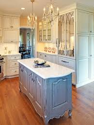 white kitchen with ornate chandeliers and island