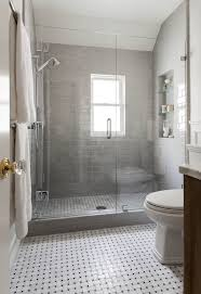 gray bathroom features a walk in shower adorned with gray subway tiles from ann sacks framing a tiled niche filled with glass shelves situated across from a