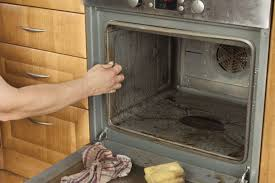 a person cleaning a very dirty oven