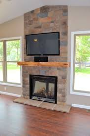 description for interior architecture fireplace stone wall and electric fireplace with tv above and wooden flooring tiles installation and light brown wall