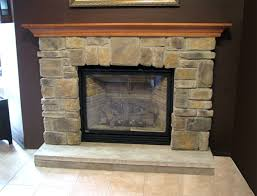 rustic cast stone fireplace surround with black wall and ceramic floor