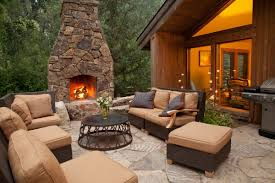 outdoor fireplace near the house with soft furniture on the patio