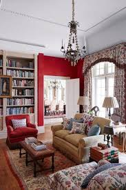 numerous intricate patterns work well against bold red walls in this library sitting room while a rug gives a cosy feel to the reading area