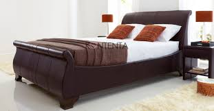 introducing the bamburgh leather sleigh bed upholstered in brown real leather featuring dark wooden feet curved head and foot board