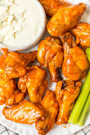 baked buffalo wings on a plate with ranch and celery