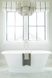 silver tiered scalloped chandelier over roll top bathtub