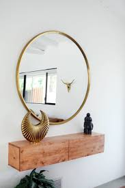 ... Minimal entryway decor with a large round mirror with gold frame