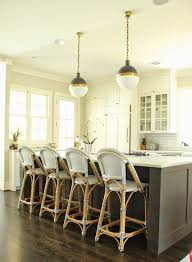 white marble framing gas stove illuminated by small hicks pendants lined with white and blue french bistro counter stools serena lily riviera stools