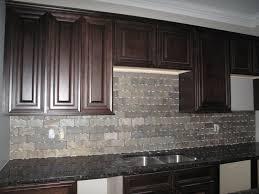 gray tile backsplash with brown cabinet