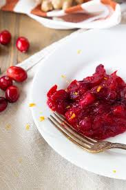 homemade cranberry sauce on a white plate with a fork resting on the edge and whole