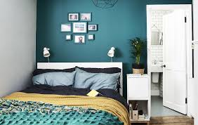 furniture for a small space. a bedroom with dark green wall and colourful bedding furniture for small space