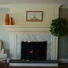 white fireplace with white tile surround and black hearth also white mantel shelf