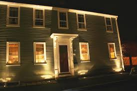 uplighting the front of a house in newburyport with flush mounted landscape lights