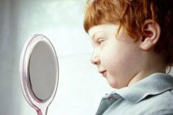 child looking in mirror. how to help your child go through the tough issues in life looking mirror