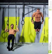 crossfit dip ring two men workout at gym dipping