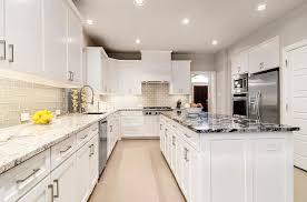 white kitchen with gray glass backsplash and granite countertop