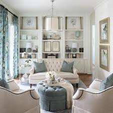 built in living room furniture. creamy whites and soft blues mix for a welcoming airy space which pairs tufted sofa ottoman with armchairs featuring nailhead trim builtin built in living room furniture