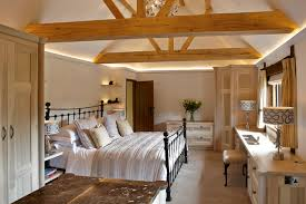 Example of a large country master carpeted bedroom design in Surrey with  gray walls