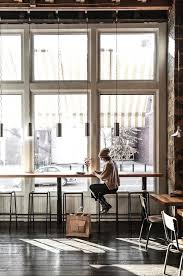 a coffee shop filled with light, hanging lamps and simple furniture