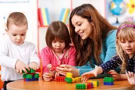 Nursery Teacher Nursery Teacher And Preschoolers Playing With Building Blocks