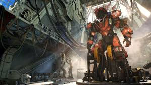 an engineer fi some equipment while an empty giant mech suit looms over the top of