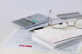 stack of envelopes with pen calculator glasses and credit card 576f5f713df78cb62cc2256c
