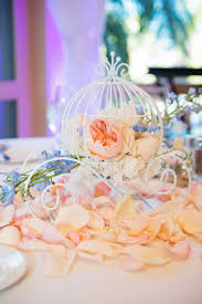 Cinderella's carriage surrounded by rose petals as a table centerpiece