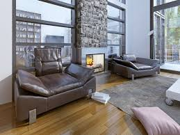 in this high rise living room a dramatic stone fireplace design helps break up two banks of windows the designer decided to give this floor to ceiling