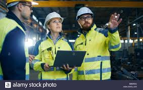 Male And Female Industrial Engineers Talk With Factory Worker While