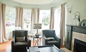 living room modern bay window decoration cream curtains black sofas light painted walls large glass